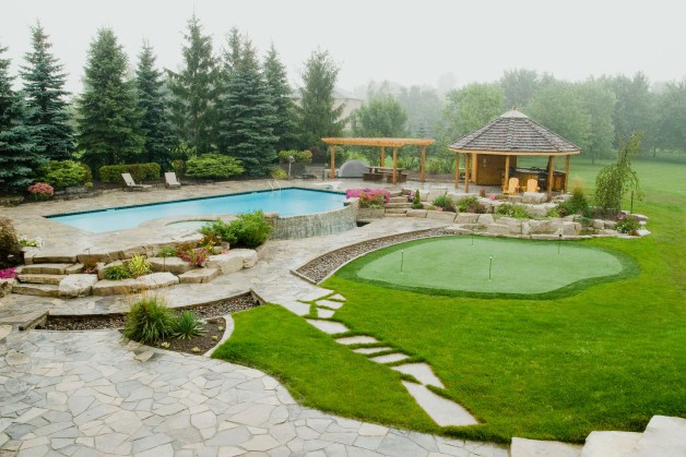 Charming-modern-backyard-hardscape-design-with-golf-filed-completed-with-gazebo-and-furnished-with-swimming-pool-area